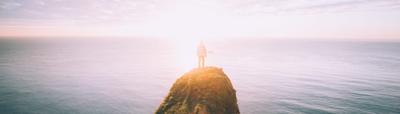 Mensch steht auf Felsen im Meer von will-van-wingerden auf unsplash.com